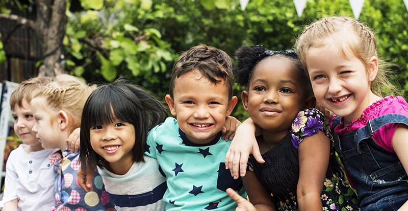 Group of young smiling children with arms around each other.