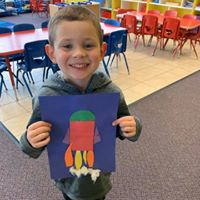 Young child smiling holding up an art project.